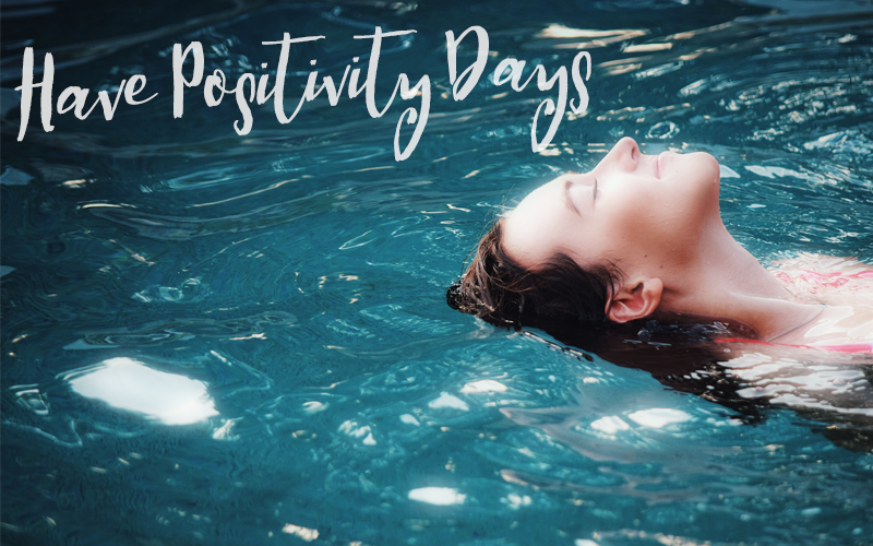 """Woman relaxing floating in water, with text """"Have Positivity Days"""""""
