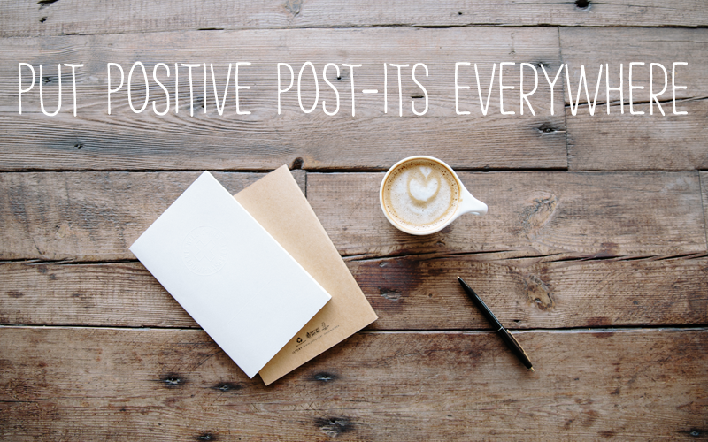 """Blank note, pen, and cup of coffee on a wooden table - caption """"Put positive Post-Its Everywhere"""""""
