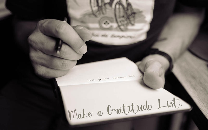 """Person with pen and paper in hand, caption """"Make a gratitude list"""""""