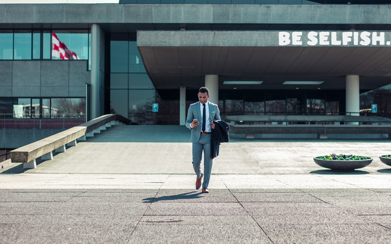 """Man in a suit walking out of a building, caption """"Be Selfish"""""""