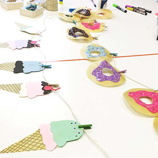 ice cream and donut dessert garland banners laid out on white desk with supplies