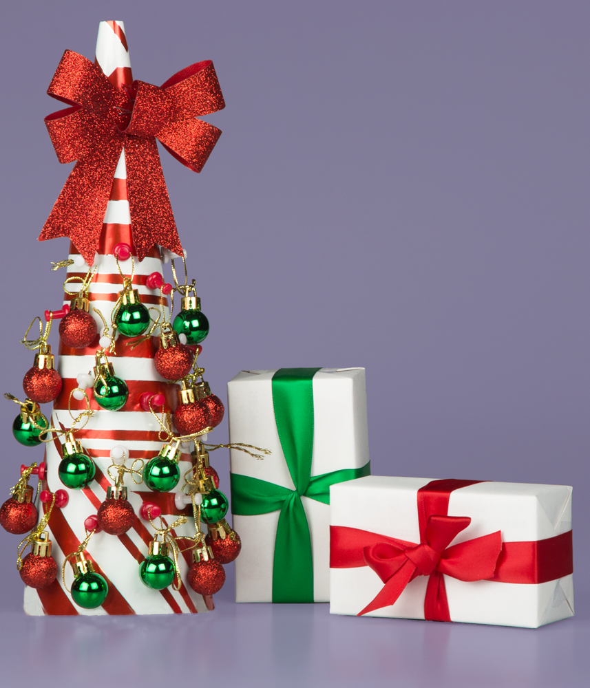 red and green themed tabletop christmas tree with green and red ribbon wrapped gifts