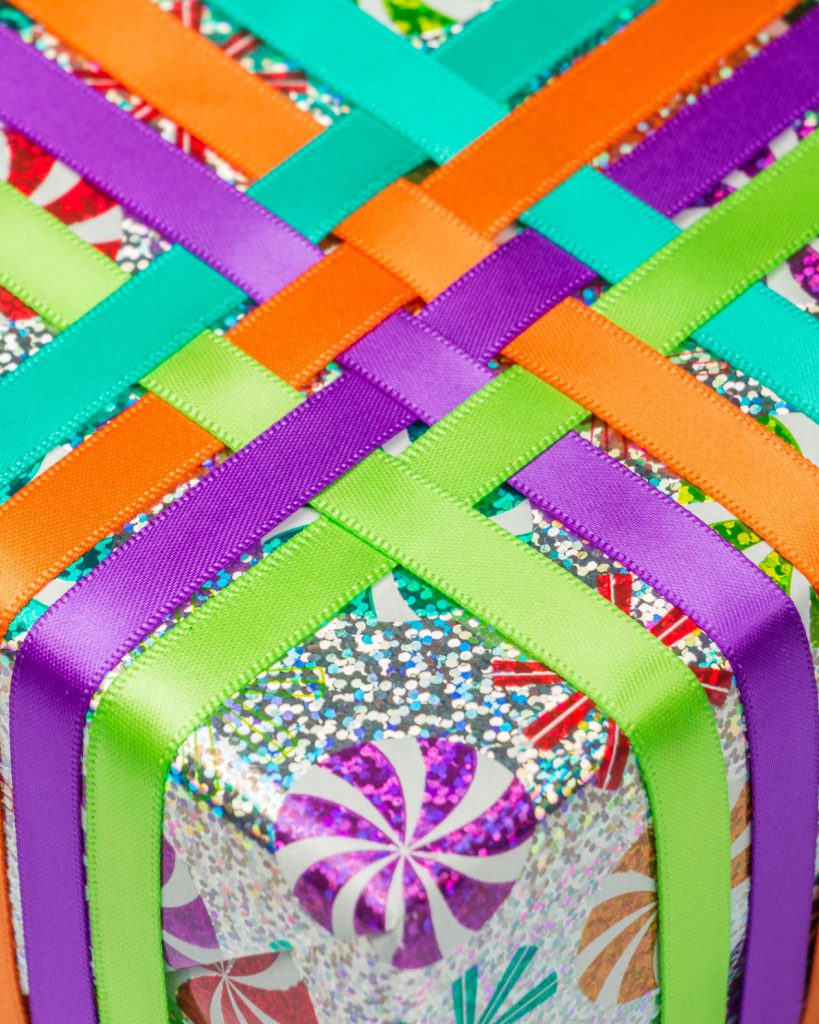 colorful holiday gift wrap with weaved ribbon design.