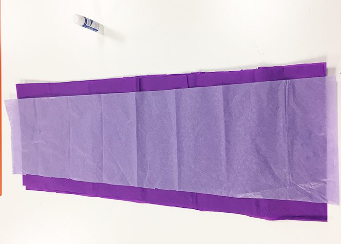 Thinner layer of white tissue paper placed on top of purple strip