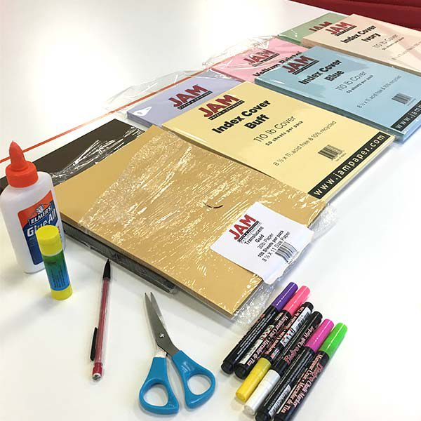 white desk with stacks of colorful cardstock, glue, colored pens, scissors, and pencil