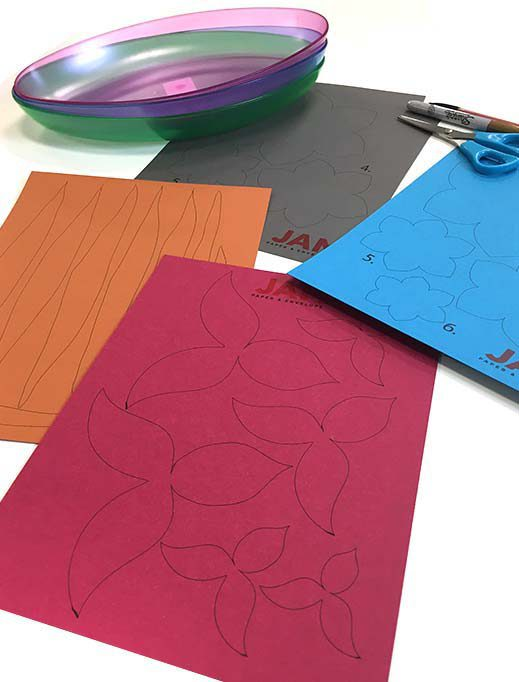 colorful paper with shapes drawn in pen, sharpie, scissors, and plastic plates