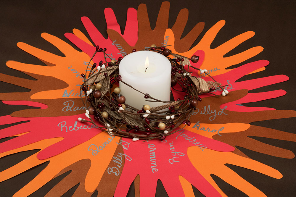 Thanksgiving centerpiece consisting of hand cutouts of fall-colored construction paper arranged in a circle with names inscribed on them in silver, and a white candle surrounded by a small wreath in the center