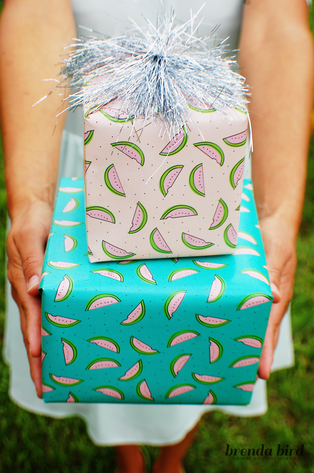 woman in skirt carrying two wrapped boxes with watermelon wrapping paper